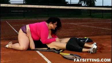 Extra large brunnette dominates her tennis teacher's face